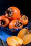 Kakis oranges mûrs dans la cuvette bleue Images stock