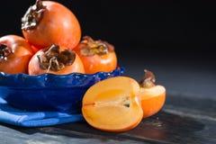 Kakis oranges mûrs dans la cuvette bleue Image libre de droits