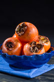 Kakis oranges mûrs dans la cuvette bleue Photos stock