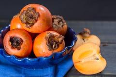 Kakis oranges mûrs dans la cuvette bleue Photo stock