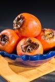 Kakis oranges mûrs dans la cuvette bleue Image stock