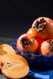 Kakis oranges mûrs dans la cuvette bleue Photos libres de droits