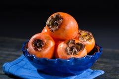 Kakis oranges mûrs dans la cuvette bleue Photographie stock