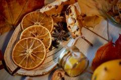 Kakor, biscotti, skivor av apelsinen, höstsidor och en krus av driftstopp eller Atmosfären av värme och hemtrevlighet arkivbilder