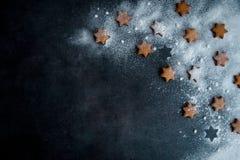 Kakor för julpepparkakastjärna på mörkret - blå bakgrund s fotografering för bildbyråer