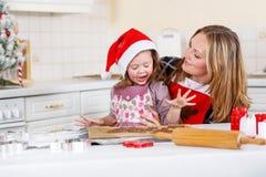 Kakor för pepparkaka för flicka för moder och för liten unge stekheta för jul fotografering för bildbyråer