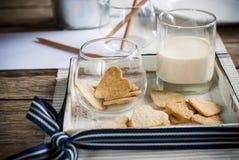 Kakor i Shape av hjärtor med mjölkar på trätabellen arkivfoton