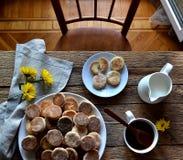 Kakor kaffe, mjölkar, blommor på en trätabell royaltyfri bild