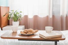 kakor, koppar och bok på tabellen arkivfoton