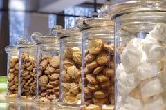 Kakor marshmallower, sötsaker i exponeringsglaskrus på shoppar fönstret arkivfoto