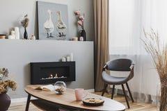 Kakor och det rosa laget rånar på träkaffetabellen i grå vardagsrum som är inre med ecospisen och chic stol royaltyfri foto