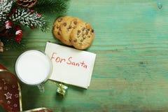 Kakor och ett exponeringsglas av mjölkar för jultomten Jul arkivfoto