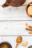 Kakor orange driftstopp, te, kanelbruna pinnar på vit träbakgrund Fotografering för Bildbyråer