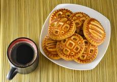 Kakor på en platta och en kopp av svart kaffe ovanför sikt arkivfoto