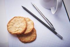 Kakor på notepaden i regeringsställning Mellanmåltid i ett arbete Blyertspenna och penna som hjälpmedel av skapelsen Arkivbilder