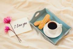 Kakor, varmt kaffe, blommor och anmärkning med texten: JAG ÄLSKAR DIG Arkivbild