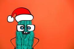 Kaktushipsterman med den santa hatten Tropiskt julbegrepp Minsta rolig konst royaltyfri foto