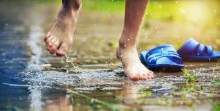 Kal fot av en barnbanhoppning in i en pöl av regn Royaltyfri Bild