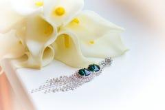 在窗台的美丽的耳环在白花Kala婚礼花束附近 免版税图库摄影
