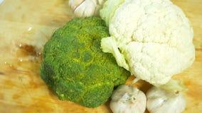 Kalafior, brokuły i czosnku przędzalnictwo na drewnianej tnącej desce, 4K zdjęcie wideo