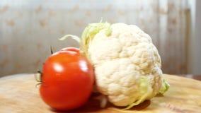 Kalafior i trzy pomidoru wiruje na drewnianej tnącej desce 4K zdjęcie wideo