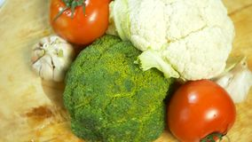 Kalafior, pomidory, brokuły i czosnek wiruje na drewnianej tnącej desce, 4K zdjęcie wideo