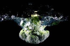 Kalafior spada w wodę, odosobnioną przeciw czarnemu tłu Obrazy Royalty Free