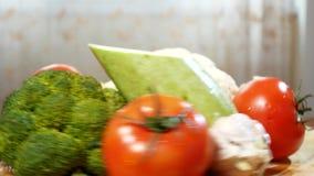 Kalafior, zucchini, pomidor, brokuły i czosnek wiruje na drewnianej tnącej desce, 4K zbiory wideo