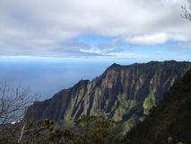Kalalau lookout on north shore  of Kauai Hawaii. Mountains meet the clouds near the ocean on Kauai Stock Images