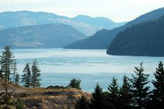Lake with mountains in background. View of Kalamalka Lake looking north in Okanagan Valley with mountains fading away into distance on hazy summer day Stock Photos