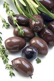 Kalamata, aromatische zwarte olijf van Griekenland met kruiden op een wit Stock Fotografie