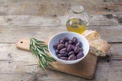 Kalamata black olives, oil, bread and rosemary garnish on rustic Stock Images