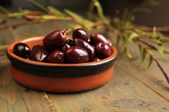 Kalamata olives. Into in a bowl on wooden table Stock Photography