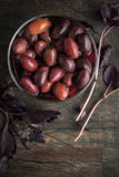Kalamata olives in   brine on the glass dish  with red basil vertical Royalty Free Stock Images