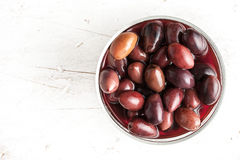 Kalamata olives in brine on the glass dish. On the white wooden table royalty free stock image