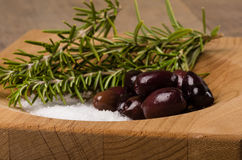 Kalamata olives and rosemary being prepared Stock Photos