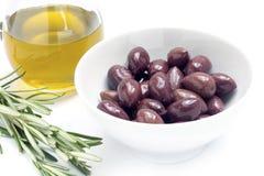 Kalamata svarta oliv i en vit bunke och olivolja, rosmaringummin Royaltyfri Bild
