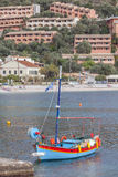 Kalami Bay. Corfu, with new holiday villas on the cliff and a traditional fishing boat moored in the foreground. The cove in north-east Corfu was made famous Royalty Free Stock Photography
