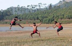 Kalaripayattu - Indian Marital art demonstration in Kerala, South India. Indian fighters with swords jumping up during Kalaripayattu Marital art demonstration in stock photography