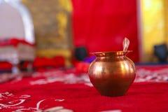 Kalash de cobre con la hoja del coco y del mango con la decoración floral imagen de archivo