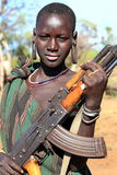 Tribal boy. Boy  from the Mursi tribe in Ethiopia protecting his herd with her gun Stock Image