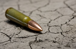 Kalashnikov bullet on desert land background Stock Images