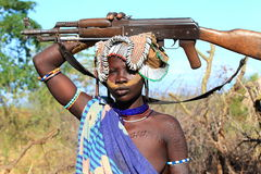 Tribal girl. Girl from the Mursi tribe in Ethiopia protecting her herd with her gun Stock Photo
