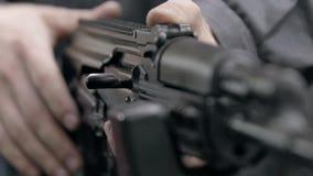 Slow motion charging rifle. Unlocking assault rifle. AK47 loading. Factory worker hand charging machine gun. Factory. Kalashnikov rifle charging. Close up of stock video