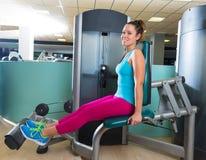 Kalberweiterungsfrau an der Turnhallenübungsmaschine Stockfoto