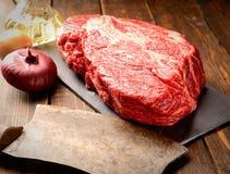 Kalbfleischsteak marmorte Basalt, ein Messer für Fleisch, hölzerner Hintergrund der Zwiebel Lizenzfreies Stockfoto