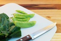 Kale, μπιζέλια, υπόλοιπα μαχαιριών στον πλαστικό τέμνοντα πίνακα Στοκ Εικόνες