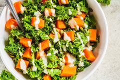 Kale and baked sweet potato salad with tahini dressing in white bowl, top view. Healthy vegan food concept