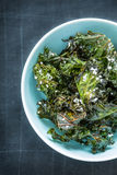 Kale chips with salt in pastel blue bowl from above Royalty Free Stock Image