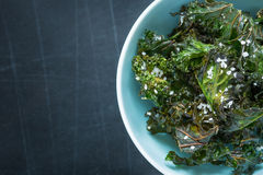 Kale chips with salt in pastel blue bowl from above Stock Photography
